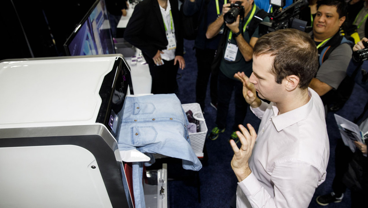 An attendee tries a FoldiMate Inc. robotic laundry folding machine during the CES Unveiled event. Patrick T. Fallon—Bloomberg via Getty Images
