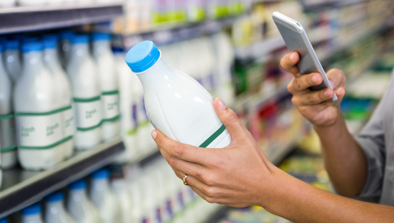 A customer scanning a bottle of milk with her phone using a scanning app